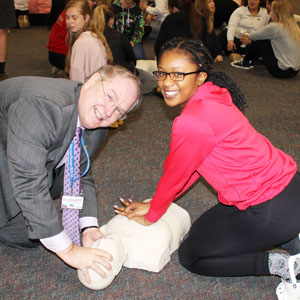 Man and girl practice CPR on dummy