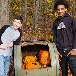 two boys standing at composter