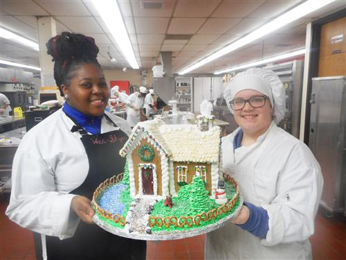 Students holding gingerbread house