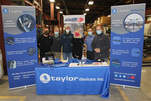 Six people standing behind table with taylor devices with banners
