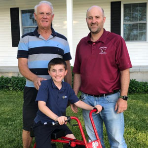 Two men and boy standing with minibike