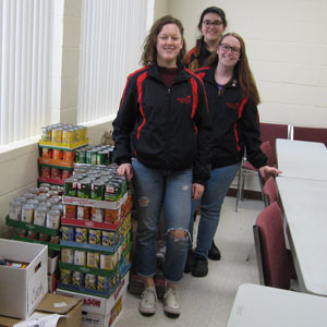 Students posing in front of canned goods