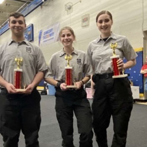 Three students holding trophies