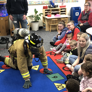 firefighter crawling on carpet in front of students