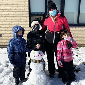 teacher and three students next to snowman