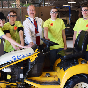 Dr. Godshall with students in front of lawn mower