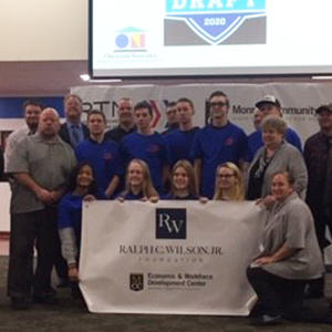 students and staff posing behind banner