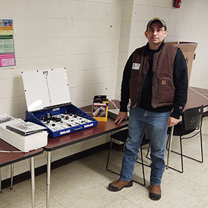 manstanding next to table with equipment